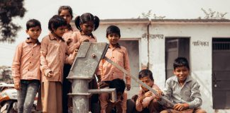 Children waiting at water pump to drink water