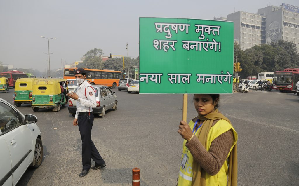 "A volunteer holds a placard which reads ""We will make a pollution free city"" at a traffic intersection usually congested, on the first day of a two-week experiment to reduce the number of cars to fight pollution in New Delhi, India, Friday, Jan. 1, 2016."